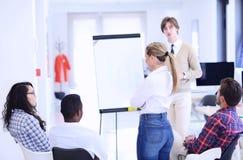Homme d'affaires présentant un exposé à ses collègues au travail se tenant devant un flipchart Photos libres de droits