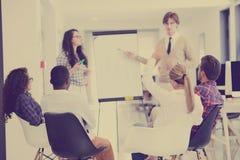 Homme d'affaires présentant un exposé à ses collègues au travail se tenant devant un flipchart Photo stock