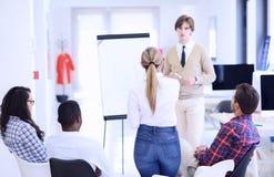 Homme d'affaires présentant un exposé à ses collègues au travail se tenant devant un flipchart Image libre de droits