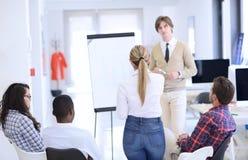 Homme d'affaires présentant un exposé à ses collègues au travail se tenant devant un flipchart Images stock