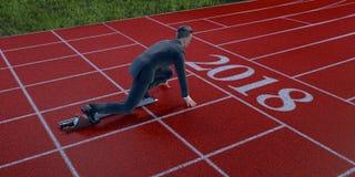 Homme d'affaires prêt à sprinter sur la ligne de départ de l'année 2018 photo stock
