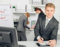 Homme d'affaires prenant des notes et des sourires photo stock