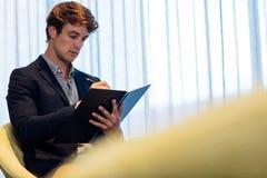 Homme d'affaires prenant des notes sur un livre Photographie stock libre de droits
