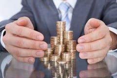 Homme d'affaires prenant soin des pièces de monnaie Images stock