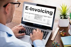 Homme d'affaires Preparing Bill On Laptop At Desk de E-facturation photo libre de droits