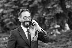 Homme d'affaires professionnel heureux attirant habillé dans le costume et verres parlant au téléphone portable dehors en parc Mo images stock
