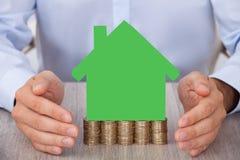 Homme d'affaires protégeant la maison modèle verte sur les pièces de monnaie empilées Photographie stock