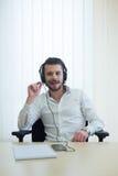 Homme d'affaires qui écoute la musique avec des écouteurs, avec un stylo dedans Photo libre de droits