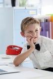 Homme d'affaires réfléchi avec la main sur le menton regardant loin par l'ordinateur portable Image stock