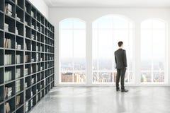 Homme d'affaires réfléchi dans le côté de bibliothèque Photos stock