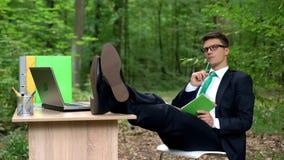 Homme d'affaires réfléchi faisant la liste des idées créatives, inspirée par nature en parc photo stock