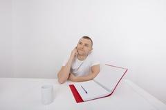 Homme d'affaires réfléchi répondant au téléphone intelligent au bureau photos libres de droits