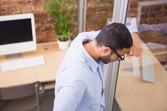 Homme d'affaires réfléchi se tenant contre le mur de verre au bureau photographie stock