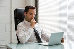 Homme d'affaires réfléchi tout en à l'aide de l'ordinateur portable Photographie stock libre de droits