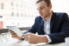 Homme d'affaires réfléchi Using Digital Tablet Images libres de droits