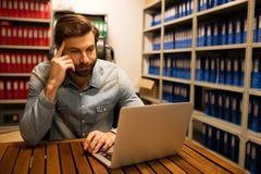Homme d'affaires réfléchi utilisant l'ordinateur portable dans la chambre de stockage de fichier Photo stock