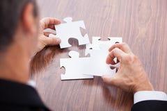 Homme d'affaires résolvant le puzzle denteux Images stock