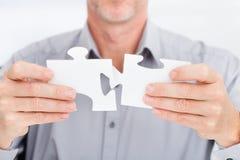 Homme d'affaires résolvant le puzzle denteux Image libre de droits