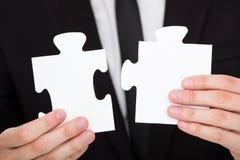 Homme d'affaires résolvant le puzzle denteux Photo libre de droits