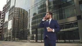 Homme d'affaires réussi dans le costume bleu tenant la tasse de café et ayant l'entretien de téléphone dehors banque de vidéos