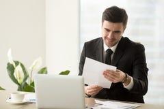 Homme d'affaires réussi de sourire tenant le document, lisant le bon Ne Images libres de droits