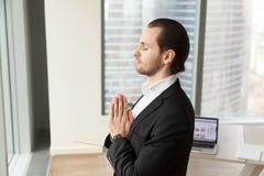 Homme d'affaires réussi méditant sur le lieu de travail dans le bureau moderne Photo stock