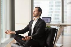 Homme d'affaires réussi méditant sur le lieu de travail dans le bureau moderne Photographie stock libre de droits