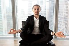 Homme d'affaires réussi méditant sur le lieu de travail dans le bureau moderne Photographie stock