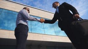 Homme d'affaires réussi passant une serviette noire à son associé près de l'immeuble de bureaux Jeune secousse masculine de collè banque de vidéos