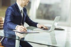Homme d'affaires réussi travaillant sur l'ordinateur portable avec des données financières sur le lieu de travail dans un bureau  Image stock