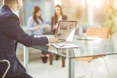 Homme d'affaires réussi travaillant sur l'ordinateur portable avec des données financières sur le lieu de travail dans un bureau  Photographie stock libre de droits