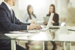 Homme d'affaires réussi travaillant sur l'ordinateur portable avec des données financières sur le lieu de travail dans un bureau  Photo stock