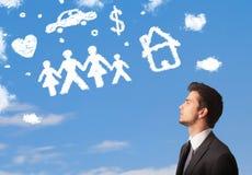 Homme d'affaires rêvassant avec des nuages de famille et de ménage Images libres de droits