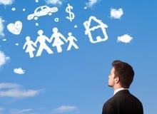 Homme d'affaires rêvassant avec des nuages de famille et de ménage Image libre de droits
