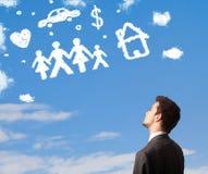 Homme d'affaires rêvassant avec des nuages de famille et de ménage Photos stock