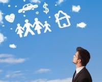 Homme d'affaires rêvassant avec des nuages de famille et de ménage Image stock