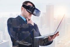 Homme d'affaires raidi dans la lecture de casque de VR de l'ordinateur portable images stock