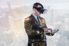 Homme d'affaires raidi dans le casque de VR travaillant sur l'ordinateur portable photographie stock libre de droits