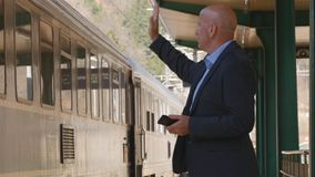 Homme d'affaires In Railway Station avec l'arrivée disponible de train de salut de téléphone portable images libres de droits