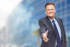 Homme d'affaires Reaching pour la secousse de main devant le bâtiment Photo stock