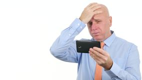 Homme d'affaires Reading Bad News de renversement sur mobile et faire des gestes nerveux banque de vidéos
