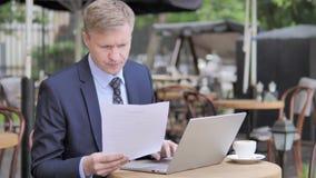 Homme d'affaires Reading Contract et ordinateur portable d'utilisation en café extérieur banque de vidéos