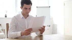 Homme d'affaires Reading Contract Papers dans le bureau photos stock