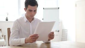 Homme d'affaires Reading Contract Papers dans le bureau banque de vidéos
