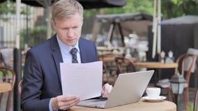 Homme d'affaires Reading Documents tout en se reposant en café extérieur banque de vidéos
