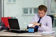 Homme d'affaires recherchant la carte par l'ordinateur portable dans le bureau Image libre de droits