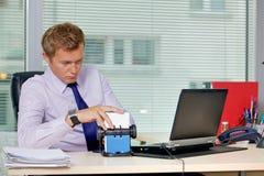 Homme d'affaires recherchant la carte par l'ordinateur portable dans le bureau Photo stock