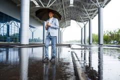 Homme d'affaires redhaired bel avec du café potable de parapluie Photos stock