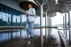 Homme d'affaires redhaired bel avec du café potable de parapluie Photos libres de droits