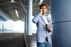 Homme d'affaires redhaired bel parlant au téléphone tenant la tasse de café dans une main Images stock